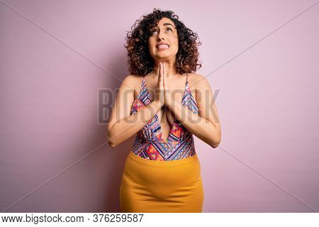 Young beautiful arab woman on vacation wearing swimsuit and sunglasses over pink background begging and praying with hands together with hope expression on face very emotional and worried. Begging.