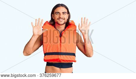 Young handsome man wearing nautical lifejacket showing and pointing up with fingers number ten while smiling confident and happy.