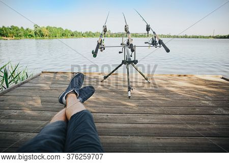 Young Fisherman Fishing On Lake Or River. Picture Of Relaxed Guy Sitting On Pier Alone And Looking A