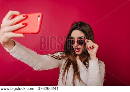 Fascinating Girl With Red Manicure Taking Picture Of Herself. Lovable Lady Touching Her Glasses Whil