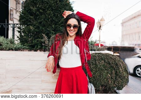 Confident Girl In Red Attire Posing With Blissful Smile. Outdoor Portrait Of Fascinating Lady In Sun