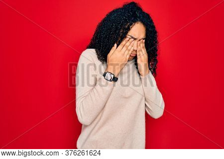 Young african american curly woman wearing casual turtleneck sweater over red background rubbing eyes for fatigue and headache, sleepy and tired expression. Vision problem