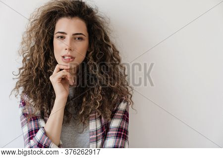 Photo of puzzled beautiful woman looking and posing at camera isolated over white background