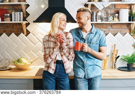 Young Happy Couple Drink Coffee In The Morning And Enjoying The Company Of Each Other In Kitchen At