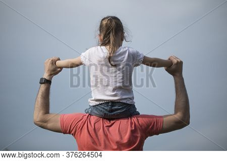 Family Values. Father And Daughter Meet The Sunset. He Will Put The Girl On His Shoulders And Hold H