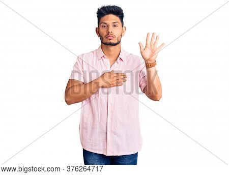 Handsome latin american young man wearing casual summer shirt swearing with hand on chest and open palm, making a loyalty promise oath