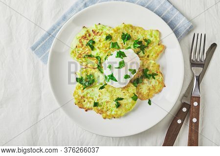 Vegetable Zucchini Pancakes With Poached Egg On White Plate. Top View
