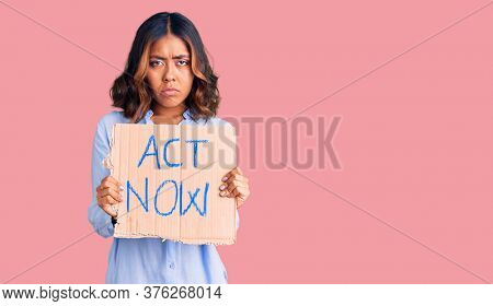 Young beautiful mixed race woman holding act now banner thinking attitude and sober expression looking self confident
