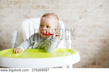 Close-up Of Teether Toddler Girl Sitting On Feeding Chair Gnawing Plastic Spoon. Cute Infant Teethin