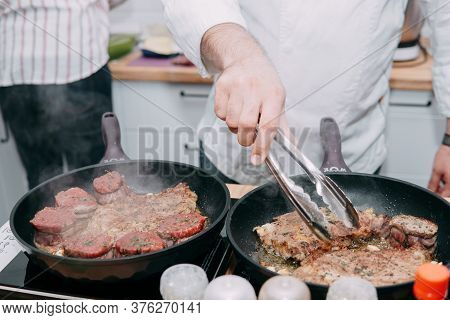 Cooking Steaks In A Frying Pan. Cooking Beef In A Cooking Master Class. The Hands Of The Chef. Minio