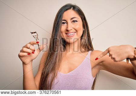 Young beautiful brunette woman holding eyelash curler over isolated white background with surprise face pointing finger to himself