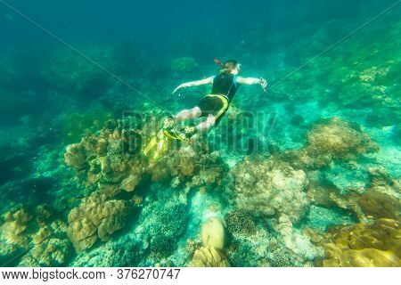 Man Snorkeling In Diving Suit In Coral Reef Of Surin Islands, Andaman Sea, North Of Phuket, Phang Ng