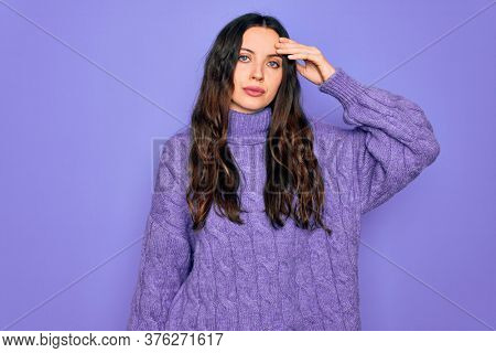 Young beautiful woman wearing casual turtleneck sweater standing over purple background worried and stressed about a problem with hand on forehead, nervous and anxious for crisis