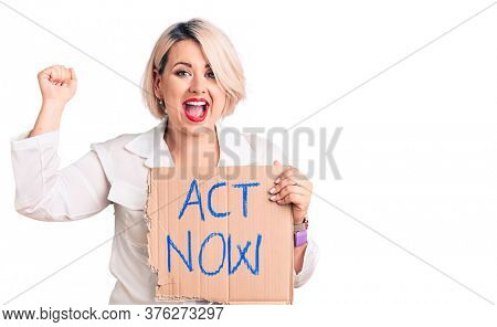 Young blonde plus size woman holding act now cardboard banner screaming proud, celebrating victory and success very excited with raised arms