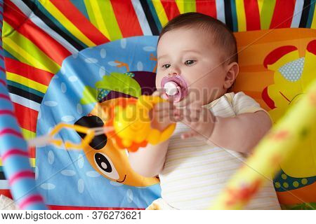 4-month-old Baby Girl Playing With Toys. Girl Pulling Hand For A Toy. Rattles For Newborns. The Kid