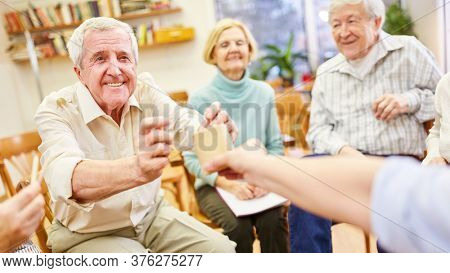 Psychotherapist plays with demented seniors in group psychotherapy