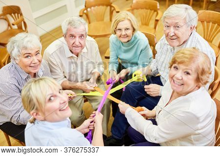Therapist and senior citizens practice exercise for cohesion with colorful ribbons