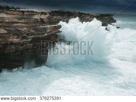 Large Waves Smash Against The Cliff Coast Of Sydney Creating Large Sprays Of Water Forced Upwards To