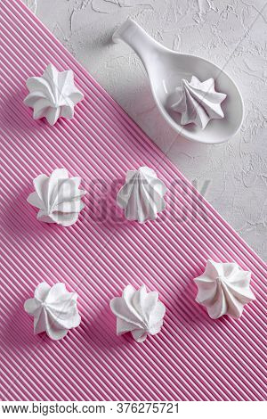 Flat Lay With White Meringue Cookies. Few Meringues Are On Pink Striped Paper Background And One   I