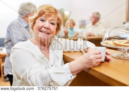 Happy elderly woman drinking espresso in the senior cafe in the retirement home