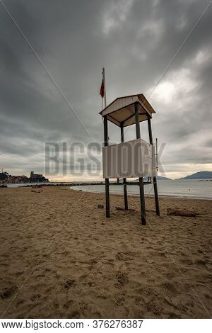 Empty Beach In Winter With A Lifeguard Tower And Red Flag Near The Small Town Of Lerici, Gulf Of La