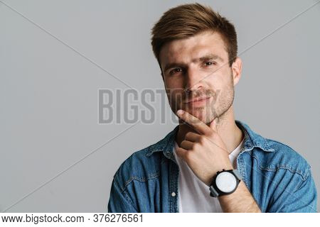 Portrait of brutal unshaven man with wristwatch posing and looking at camera isolated over grey background