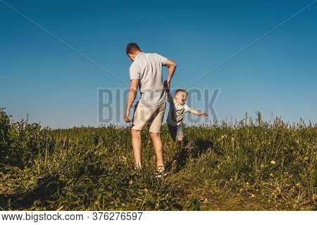 Father Holding Son Like Plane Outside. Blue Sky Background, Front View.