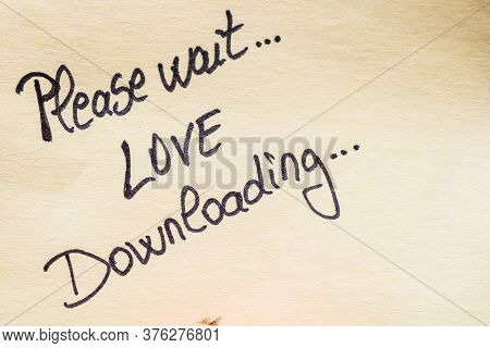 Please Wait Love Downloading Handwriting Text Close Up Isolated On Yellow Paper With Copy Space.