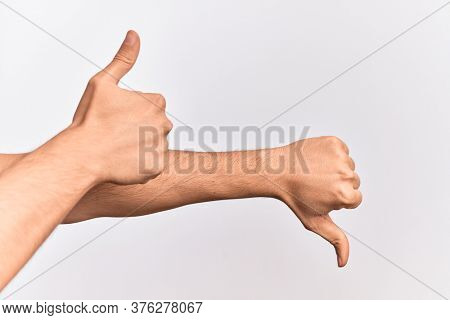 Hand of caucasian young man showing fingers over isolated white background showing disagree and agreement with thumbs up and thumbs dow, mixed emotions idea