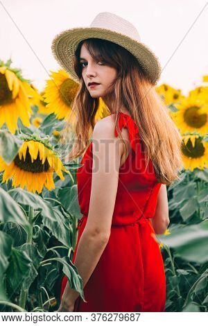 Woman With Red Dress And Hat In Sunflowers Field