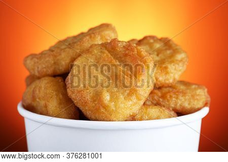 Bucket With Delicious Chicken Nuggets On Orange Background, Closeup
