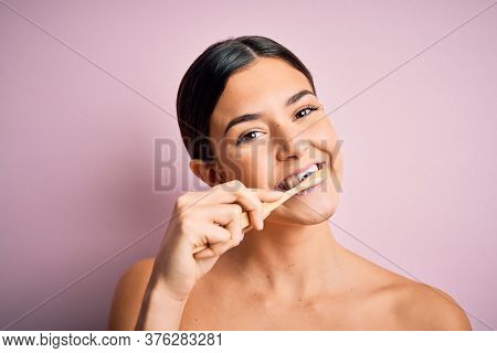 Young beautiful brunette woman brushing her teeth using tooth brush and oral paste, cleaning teeth and tongue as healthy health care morning routine