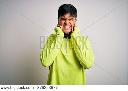 Young handsome sportsman doing sport wearing sportswear over isolated white background covering ears with fingers with annoyed expression for the noise of loud music. Deaf concept.