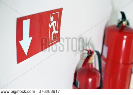 Emergency Exit Sign And Fire Extinguishers On White Wall, Closeup