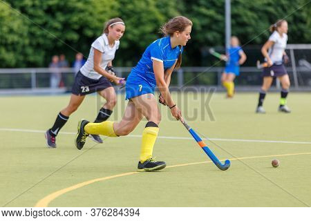 Young Women Playing Field Hockey Game On The Pitch