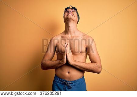 Young handsome man shirtless wearing swimsuit and swim cap over isolated yellow background begging and praying with hands together with hope expression on face very emotional and worried. Begging.