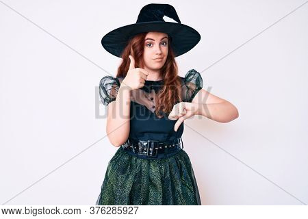 Young beautiful woman wearing witch halloween costume doing thumbs up and down, disagreement and agreement expression. crazy conflict