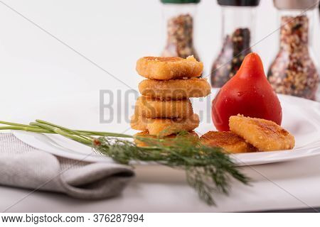 Chicken Nuggets In A Column On A Plate With Tomato. On The Table On A White Plate, Chicken Nuggets W