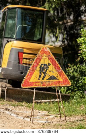 Work In Progress, Closeup Of An Old Triangular Road Sign On The Roadside With A Small Earthmover. It