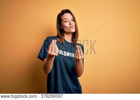 Young beautiful brunette girl doing volunteering wearing t-shirt with volunteer message word doing money gesture with hands, asking for salary payment, millionaire business
