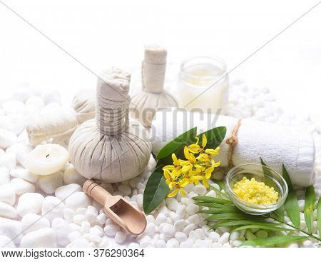 Spa setting with Green palm, bottles of essential oil with , herbal ball, salt in bowl ,candle , herbal ,ball ,spoon on pile of white stones ,yellow flower,