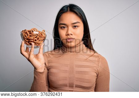 Young asian girl holding bowl with baked german pretzels over isolated white background with a confident expression on smart face thinking serious