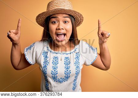Young beautiful asian girl wearing casual t-shirt and hat standing over yellow background smiling amazed and surprised and pointing up with fingers and raised arms.