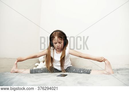 The Girl Sits In Big Headphones And Looks At The Smartphone Screen, Sitting On Her Bed. Preschooler
