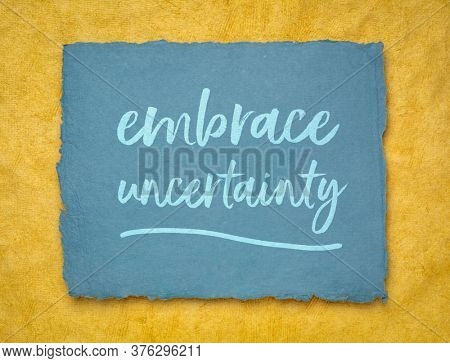 embrace uncertainty motivational note - handwriting on a handmade rag paper, unknown future, change, risk and chance concept