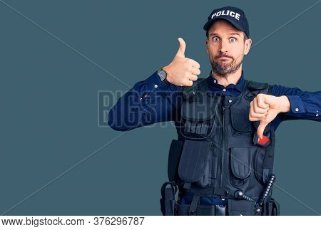 Young handsome man wearing police uniform doing thumbs up and down, disagreement and agreement expression. crazy conflict