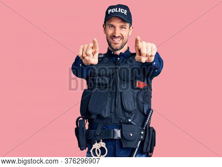 Young handsome man wearing police uniform pointing to you and the camera with fingers, smiling positive and cheerful
