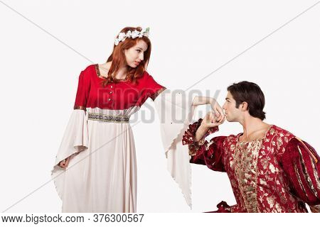 Young man in old-fashioned costume kissing princess's hand against gray background
