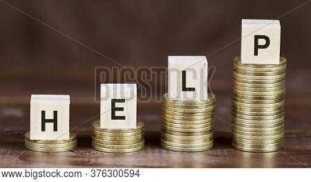 Coronavirus Financial Stimulus, Aid Package Concept, Gold Money Coins With Help Word On Wooden Cubes