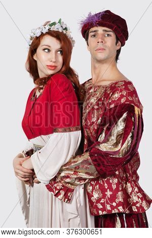 Young couple in periodic costumes against gray background